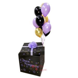Черная коробка с сиреневой надписью и черными сиреневыми и золотыми шарами